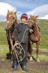 12063604-Казахский-мальчик-держит-поводья-двух-лошадей-на-паст�
